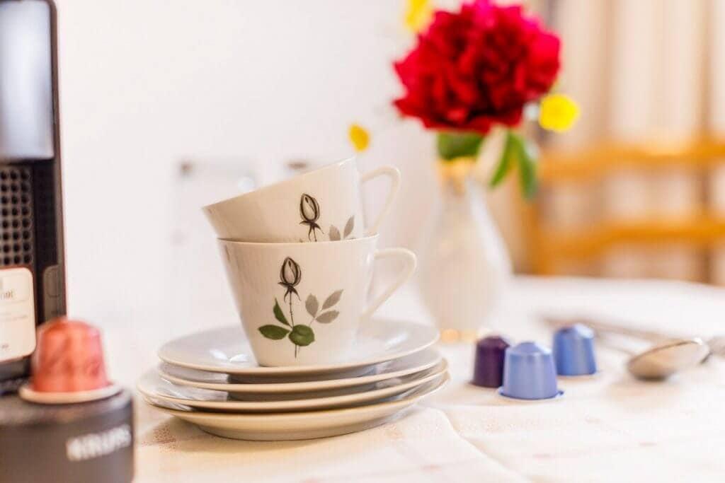 Kaffeetassen mit Kapselmaschine auf Tisch