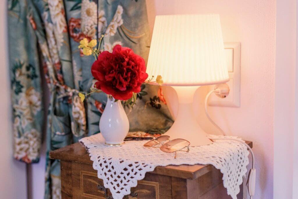 Schöne, dekorative Elemente im Zimmer: Blume mit Porzellanvase und Retrolampe