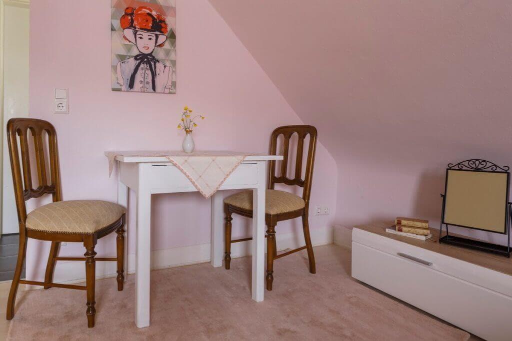 Kleiner, gemütlicher Esstisch mit Dekoration, Tischdecke und Retro-Stühlen