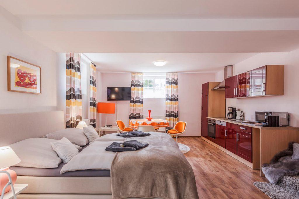 Wohn-Schlafraum mit 1,60 Boxspring-Bett, original 70er Designer-Schalenstühlen und -Tisch, passende Lampe, luxuriöse, voll-ausgestattete Einbauküche und Lounge-Bereich
